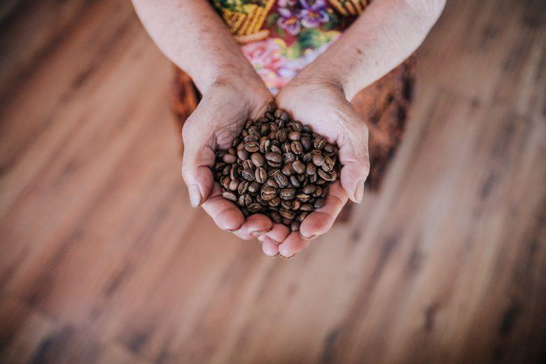 Une paire de mains tenant des grains de café
