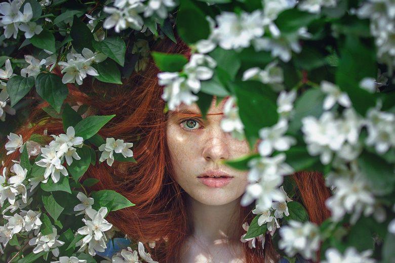 peau sensible femme derrière buisson fleurs